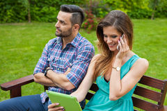 Couple sitting on the bench. Girl is talking by the phone Royalty Free Stock Photos