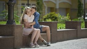 Couple sitting on bench guy, hugging shy girl at first date, romantic mood. Stock footage stock footage