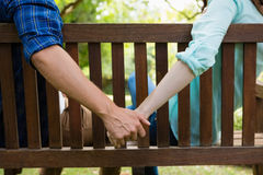 Couple sitting on bench and holding hand in garden Stock Images