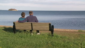 A couple sitting on a bench looking out to a large rock in the ocean (2 of 2. A view or scene on the water