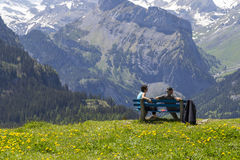Couple sitting on bench observing amazing view of Swiss Alps and meadows near Oeschinensee (Oeschinen lake), on Bernese Oberland, Stock Image