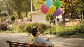 Couple sitting on a bench in the park with balloons stock video footage