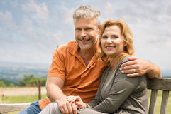 Couple Sitting On Bench. Portrait Of Happy Mature Couple Sitting On Bench Outdoor And Looking At Camera Royalty Free Stock Photography