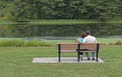 Couple Sitting On a Bench In Spring. Couple In Love Sitting On A Park Bench in Spring Stock Photo