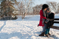 Couple Sitting On Bench In Winter Stock Images