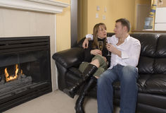 Couple sitting on black couch Stock Image