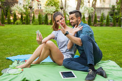 Couple sitting on the blaket, spending nice time and taking self Royalty Free Stock Image
