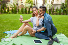 Couple sitting on the blaket, spending nice time and taking self Royalty Free Stock Images