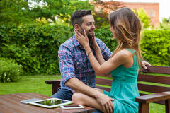 Couple sitting on the blanket in the garden, using tablet and sm Stock Image