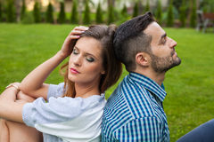 Couple sitting on the blanket in the garden, using tablet and sm Royalty Free Stock Images