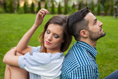 Couple sitting on the blanket in the garden, using tablet and sm Stock Images