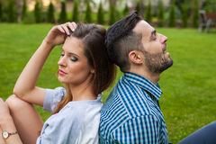 Couple sitting on the blanket in the garden, using tablet and sm Royalty Free Stock Photography