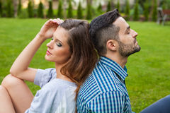 Couple sitting on the blanket in the garden, using tablet and sm Royalty Free Stock Photo