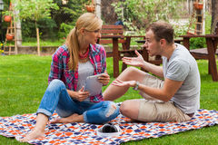Couple sitting on a blanket with tablet pc at summer green park. Royalty Free Stock Photography