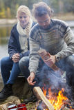 Couple Sitting By Bonfire On Lakeshore Stock Photography