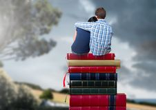 Couple sitting on Books stacked by romantic nature landscape Royalty Free Stock Photos