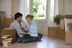 Couple Sitting With Boxes And Books At Home Royalty Free Stock Image