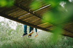 Couple sitting on the bridge Stock Images