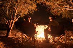 Couple sitting at burning camp fire in the night. Camping in the forest under starry sky, Namibia, Africa. Summer adventures and e royalty free stock images