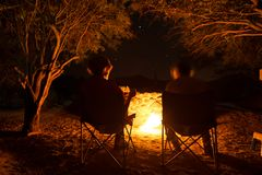 Couple sitting at burning camp fire in the night. Camping in the forest under starry sky, Namibia, Africa. Summer adventures and e