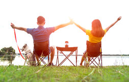 Couple sitting at burning camp with your pet dog near river on the sunset, so enjoy and happy sunny day. Royalty Free Stock Photo
