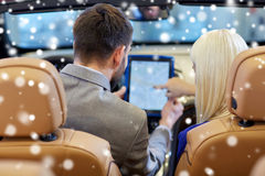 Couple sitting in cabrio car with tablet pc Stock Photos