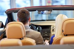 Couple sitting in cabriolet car at auto show Stock Photos