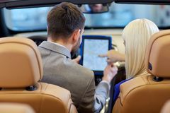 Couple sitting in cabriolet car with tablet pc Royalty Free Stock Image