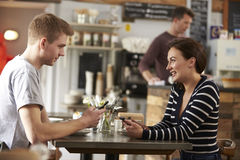 Couple sitting in cafe using smartphones look at each other Stock Photos