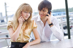 Couple sitting in cafe using their cell phones Royalty Free Stock Image