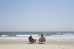 A couple sitting on canvas chairs. At beach Royalty Free Stock Photos