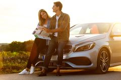 Couple sitting on car lost and looking at map. Full length portrait of couple sitting on car lost and looking at map Stock Photography