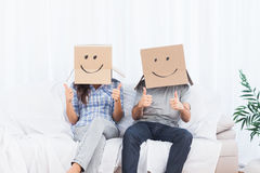 Couple sitting with cardboard boxes on head giving thumbs up Royalty Free Stock Images