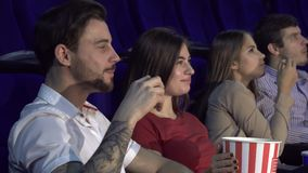 Two young couples watching the premiere of a new film. The couple are sitting in the cinema. They eat popocorn and discuss the film. Couples look happy and stock video footage
