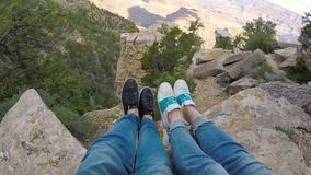 Couple sitting on a cliff. Of Grand Canyon stock footage