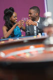 Couple sitting clinking glasses at the roulette table Royalty Free Stock Image