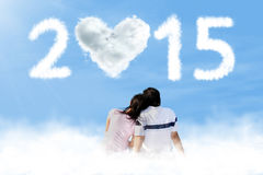 Couple sitting on cloud with number 2015 Royalty Free Stock Image