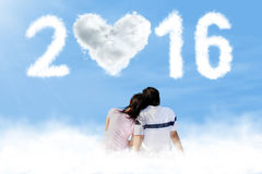 Couple sitting on the cloud with numbers 2016 Royalty Free Stock Photography