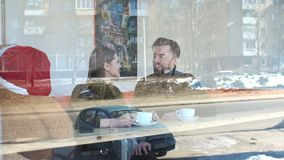 Couple sitting in a coffee shop and drinking coffee, the view through the window stock footage