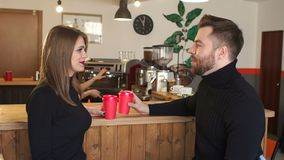 Couple sitting in a coffee shop near the bar, drinking hot coffee and talking. stock footage
