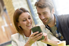 Couple sitting in coffee shop using smartphone Stock Photos