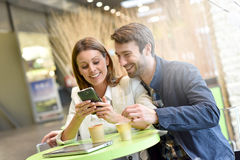 Couple sitting at coffee shop using smartphone Stock Photo