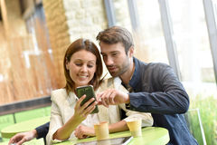 Couple sitting at coffee shop websurfing Royalty Free Stock Photos