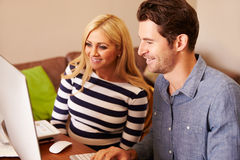Couple Sitting At Computer In Home Office Shopping On Line Royalty Free Stock Image