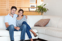 Couple sitting on a couch Stock Images
