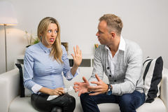 Couple sitting on couch and  arguing Royalty Free Stock Image