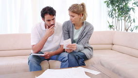 Couple sitting on a couch while checking their bills stock video