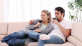Couple sitting on the couch while drinking wine. In their living room stock video footage