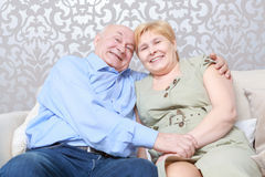 Couple sitting on a couch Stock Photos