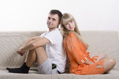 Couple sitting on the couch with his back to each other and looking in the frame Stock Photos